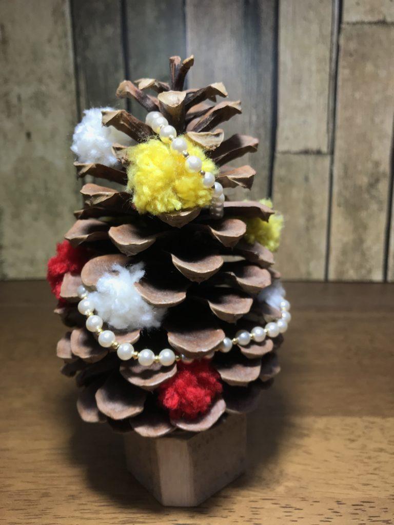まつぼっくりを使ったクリスマスツリーを制作してみました。 毛糸のぼんぼりとパールを飾りに使用しています。 取り外し可能ですので、シーズン終われば素朴なツリーになります。 パールの飾りはネックレスとして使用できます。